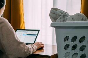 Person working next to laundry basket: our new blended on and offline lives